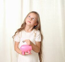 Free Little Blond Girl Puts Coin Into Piggy Moneybox Royalty Free Stock Photo - 27029975
