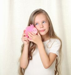 Free Little Blong Girl Hearing Money In Piggy Moneybox Royalty Free Stock Images - 27029989