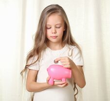 Little Blond Girl Puts Coin Into Piggy Moneybox Stock Image