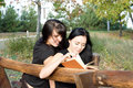 Free Girls Sitting Reading A Book Royalty Free Stock Photo - 27036015