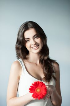 Young Smiling Casual Girl With Red Flower Stock Image