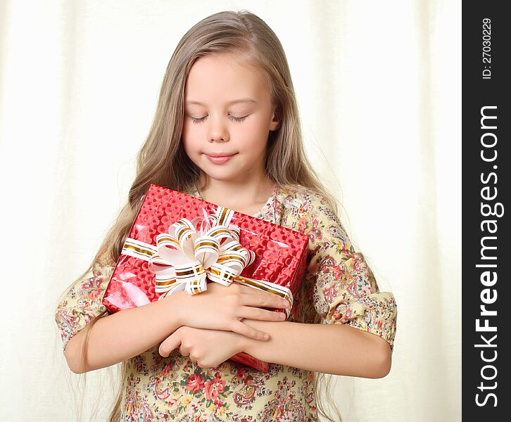 Little blond girl holding a red glamorous gift
