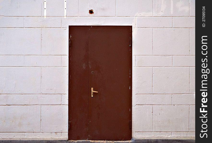 Rusty metal door in beige block wall