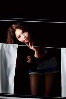 Girl In The Window With Curtains Dark Background Royalty Free Stock Photography