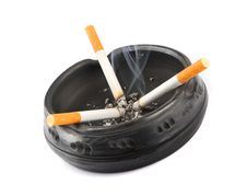 Free Three Lit Cigarettes In A Black Ashtray Royalty Free Stock Photo - 27122725