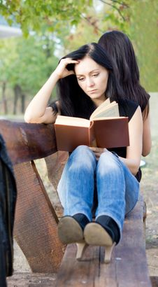 Girl Reading A Book On A Bench Royalty Free Stock Image