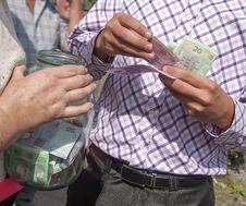 Free Man Puts The Money A  Jar Royalty Free Stock Photo - 27202605