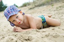 Free Little Boy Lying On The Sand Royalty Free Stock Photography - 27214167