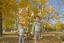 Free Two Little Boys Throw Colorful Leaves In Air Stock Photo - 27254120
