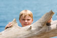 Free Boy Looking Over Driftwood Royalty Free Stock Photography - 2739467