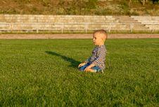 Small Boy Kneeling In Green Grass Stock Photos