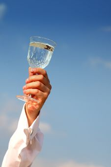 Glass Of Water In Hand On Blue Sky Stock Images