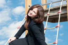 Young Business Woman Sitting On Ladder And Smiling Royalty Free Stock Images
