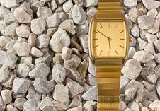 Free False Gold Wristwatch On The Gravel Royalty Free Stock Photo - 27348525