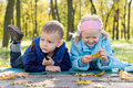 Free Small Children Relaxing In A Park In Autumn Royalty Free Stock Image - 27374146
