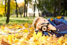 Free Small Boy Playing With A Slr Camera Stock Photography - 27375492