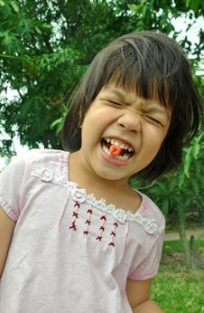 Asian Child Girl Eating Cherry From The Garden Stock Photos
