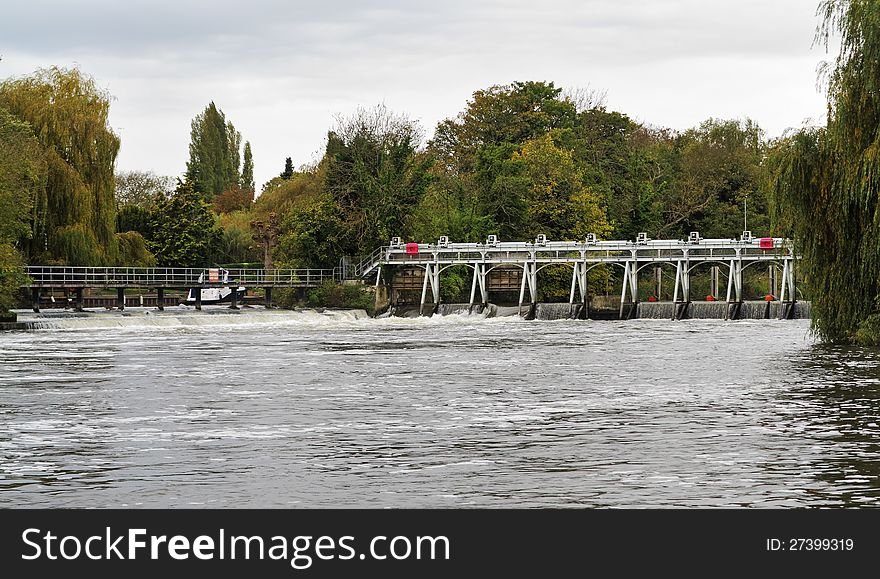 Weir and sluice gate on a swollen River Thames