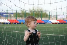 The Boy In A Grid Of A Gate Stock Image