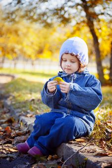 Free Little Curly Girl Sits In Autumn Park Stock Images - 27461554