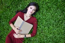 Woman Lying On Green Grass With  Book Stock Image