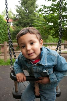 Little Cute Boy Playing On A Swing Stock Photo