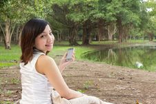 Asian Woman With Mobile Phone And Sitting At Park Stock Image