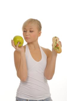 Free Slim Woman Choosing Between Apple And Hamburger Stock Photo - 27679160