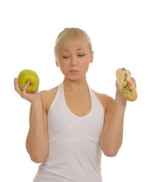 Free Slim Woman Choosing Between Apple And Hamburger Stock Photo - 27679190