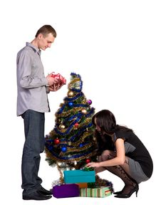 Men And Women Decorates The Christmas Tree Stock Photo