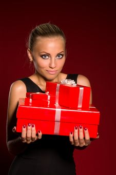 Girl In A Black Dress With Gifts In Hands Stock Images