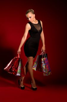 Sexy Girl In A Black Dress With Bags In Hands Stock Photo