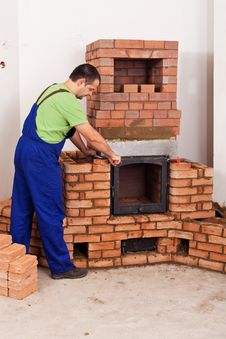 Free Worker Mounting Door To A Masonry Heater Stock Image - 27825531
