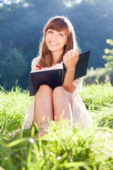 Free Woman With A Book On Green Meadow Laughs Stock Images - 27830544