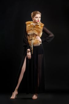 Woman In Fur Coat Over Black Background Posing Stock Image