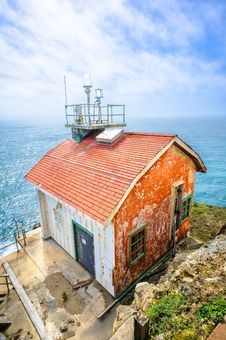 Old House On The Edge And The Blue Ocean Stock Photo