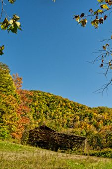An Old Barn Sits Among Fall Leaves And A Blue Sky. Stock Photography