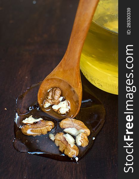 Wallnuts in honey on wooden background with wooden spoon and hon