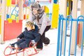 Free Mother Pushing Her Son On A Winter Sled Stock Photo - 28358920