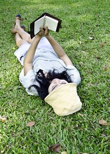 Young Woman Reading A Book In Park Stock Photo