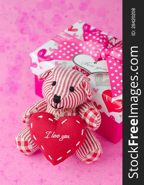 Teddy bear with a heart in the hands near a gift box and bokeh