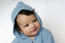 Newborn Baby Wearing Blue Cardigan Smiles Stock Photography