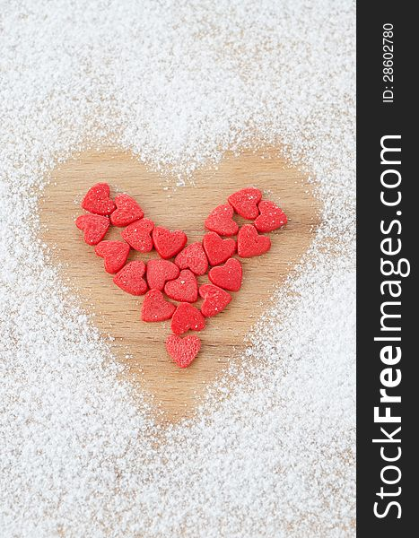 Sugar hearts in the form of heart on a board sprinkled with powd
