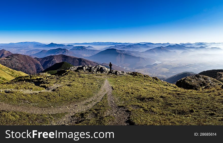 Silhouette of a man overlooking misty mountains