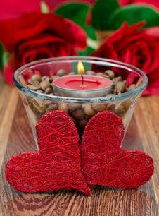 Red Candle In A Glass Cup With Coffee Beans And Two Hearts Stock Photos