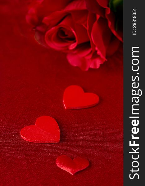 Different Sized Hearts And Red Roses On Red Background For