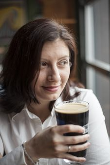 Free Young Woman With Beautiful Brown Eyes Drinking A Pint Of Stout Stock Image - 28942901
