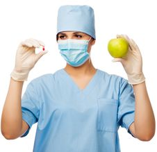 Young Doctor Holding Pill And Apple Royalty Free Stock Images