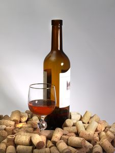 A Glass Of Wine, A Bottle, And Many Corks Stock Photos
