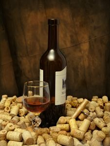 A Glass Of Wine, A Bottle, A Corkscrew And Many Corks Royalty Free Stock Image